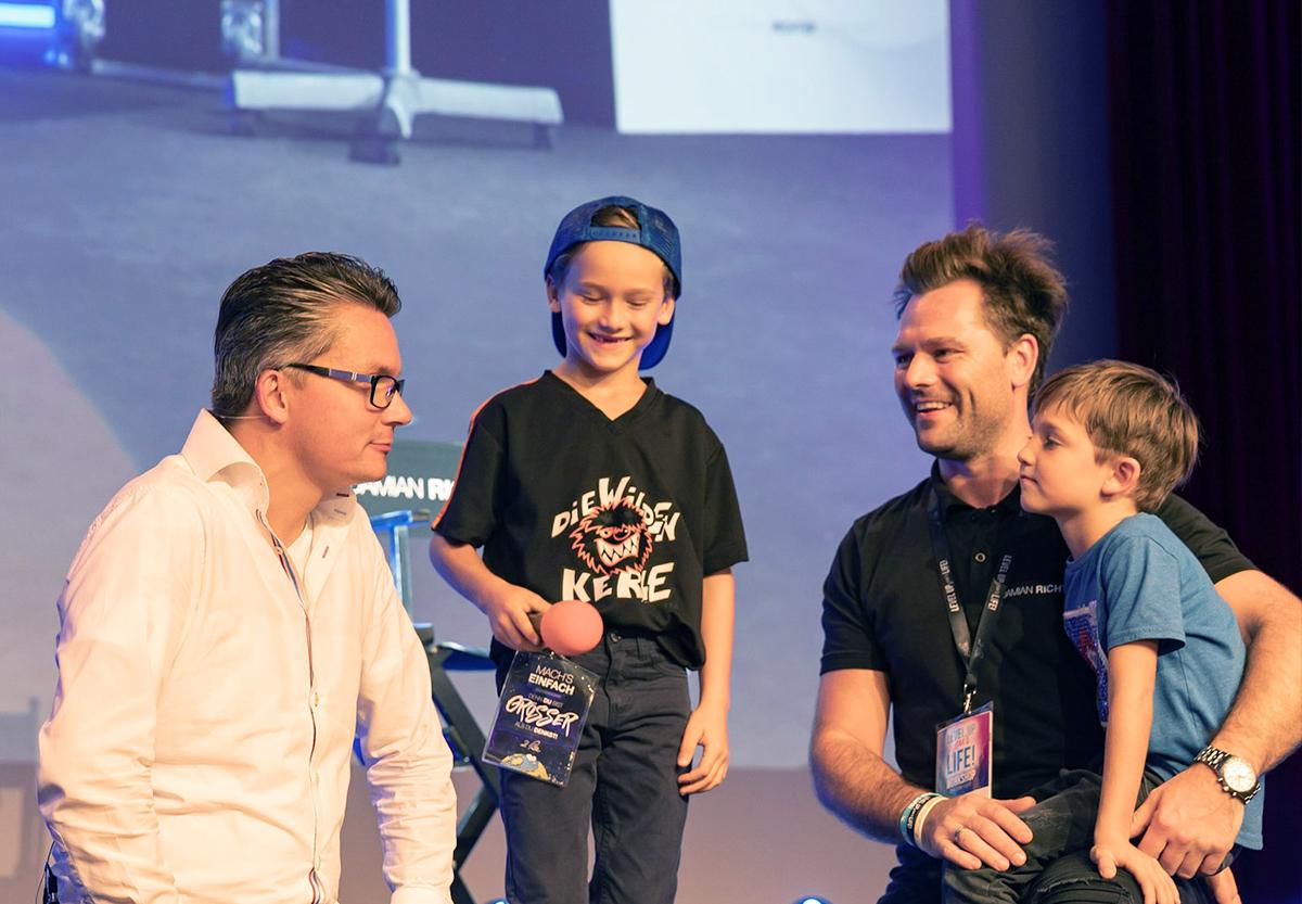 Life Design Academy Damian Richter mit Phil Schartner und Kindern auf der Bühne