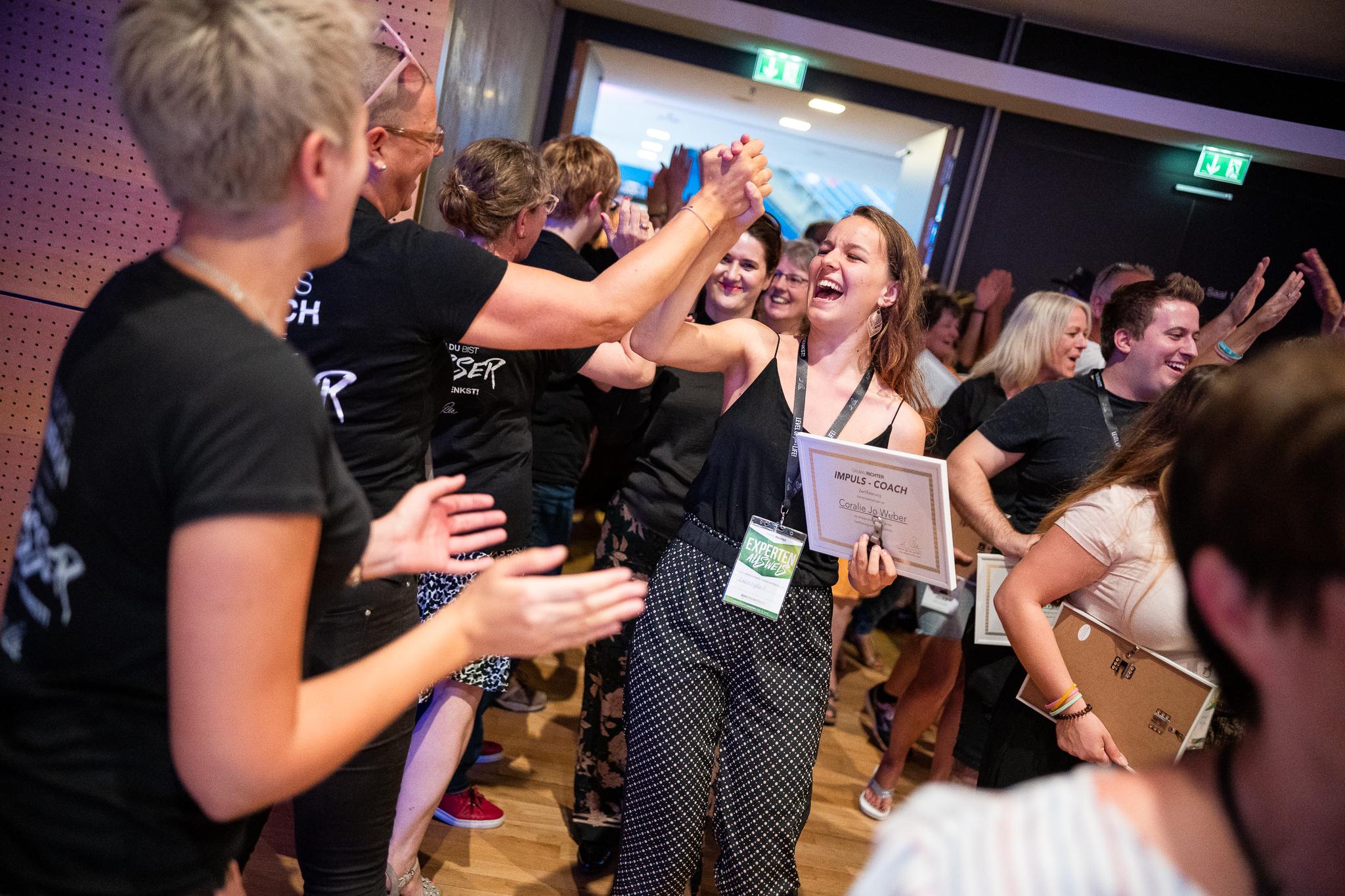 Teilnehmerin freut sich über ihr Impuls-Coach-Zertifikat