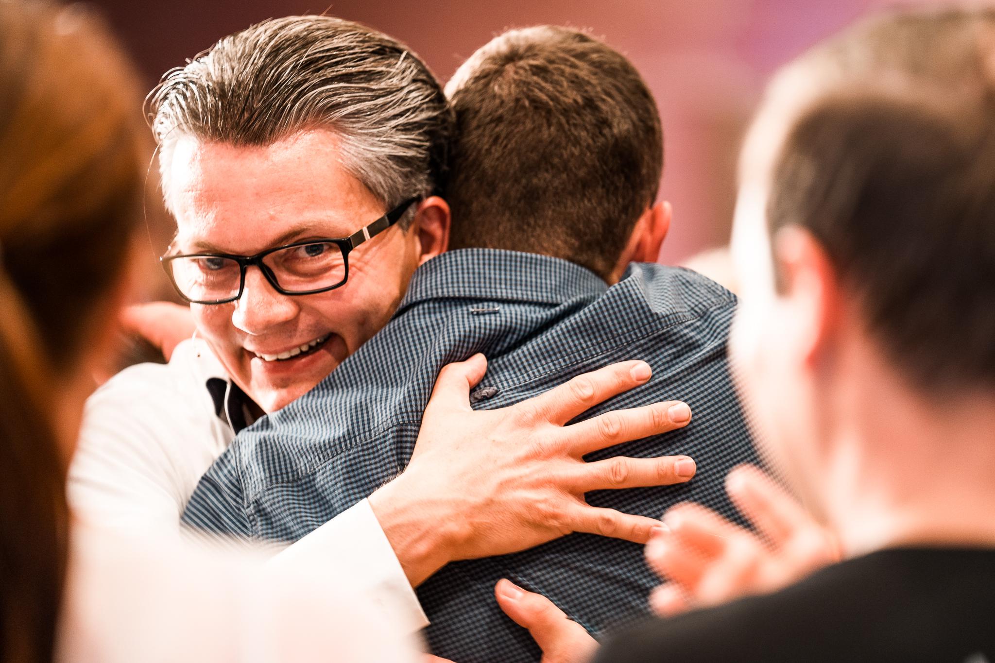 Damian umarmt Teilnehmer von Coachingausbildung