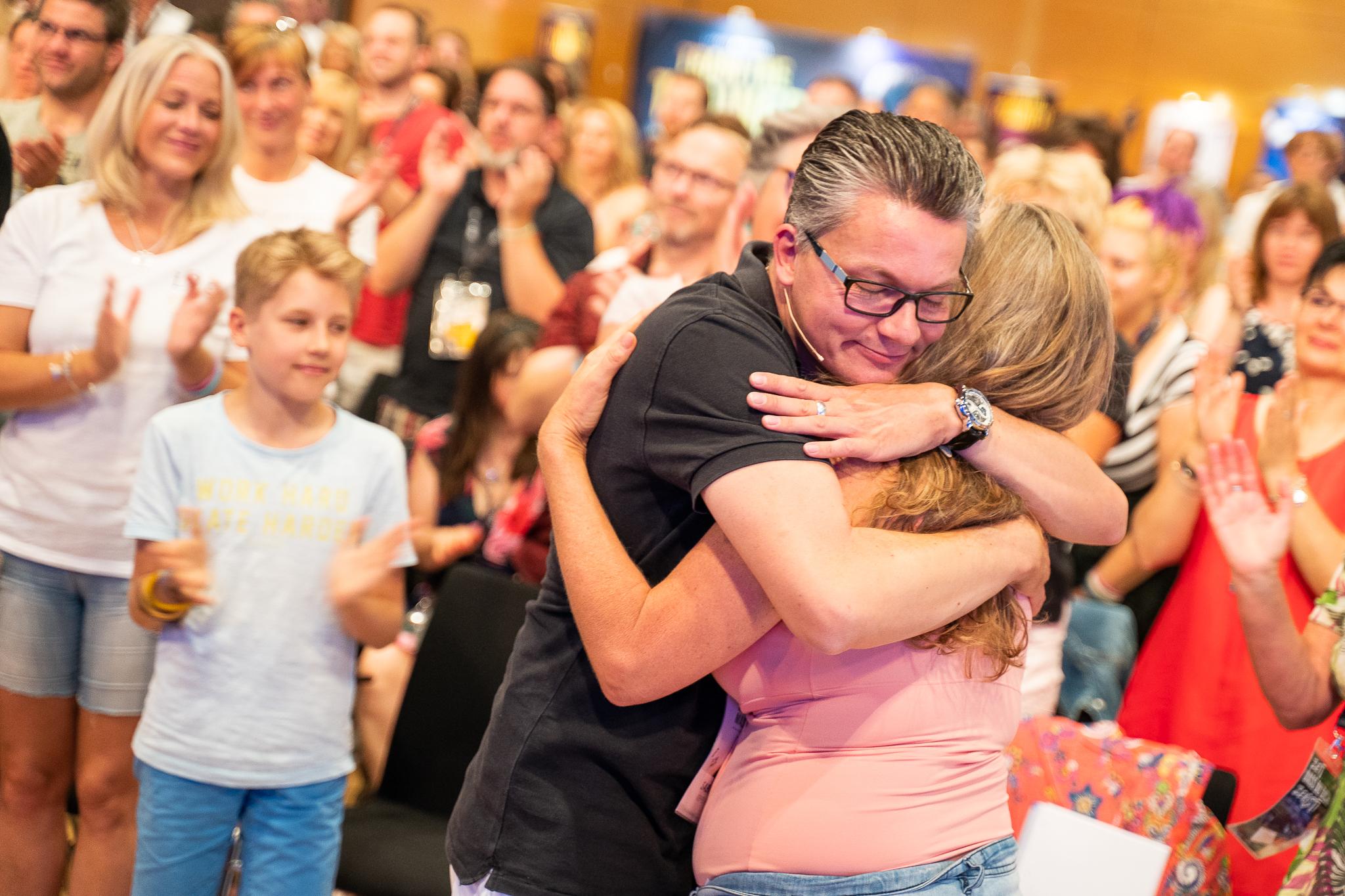 Impuls-Coach: Damian umarmt Teilnehmerin